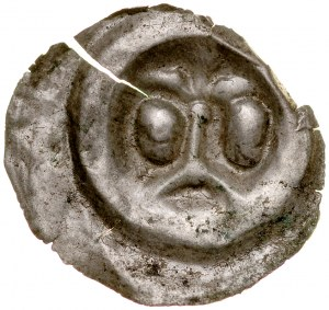 Brakteat guziczkowy II poł. XIII w., nieokreślona dzielnica, Av.: Lilia na długim słupie oparta o łuk, pod bokach dwie głowy.