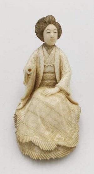 Figurka siedzącej kobiety